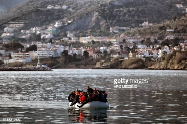 TOPSHOT Migrants and refugees on a rubber boat arrive at the northern island of Lesbos after crossing the Aegean sea from Turkey in Mytilene on...
