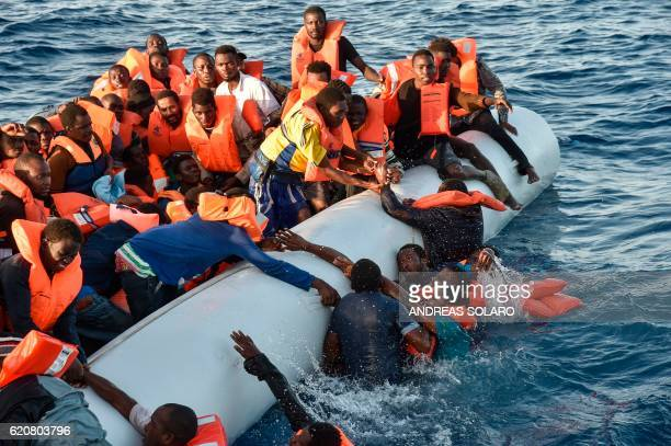 TOPSHOT Migrants and refugees panic as they fall in the water during a rescue operation of the Topaz Responder rescue ship run by Maltese NGO Moas...