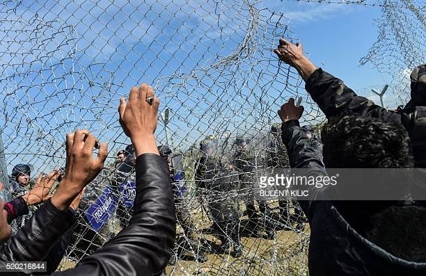TOPSHOT Migrants and refugees pull down the fence during clashes with Macedonian soldiers for the reopening of the border near their makeshift camp...