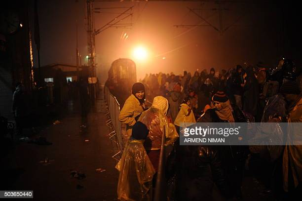 Migrants and refugees queue to board a train at a train station in the southern Serbian town of Presevo on January 6 2016 The International...