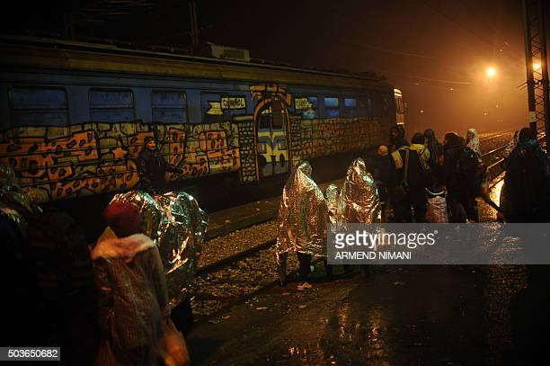 Migrants and refugees queue to board a train under heavy rain at a train station in the southern Serbian town of Presevo on January 6 2016 The...