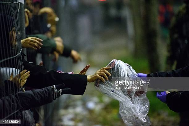 Migrants and refugees reach through a fence for clothes and food from volunteers as they wait to cross the SlovenianAustrian border in Sentilj on...