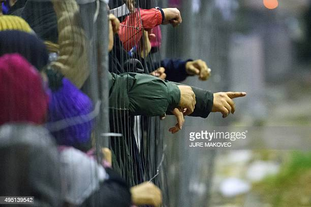 Migrants and refugees reach through a fence for food and clothes from volunteers as they wait to cross the Slovenian-Austrian border in Sentilj on...