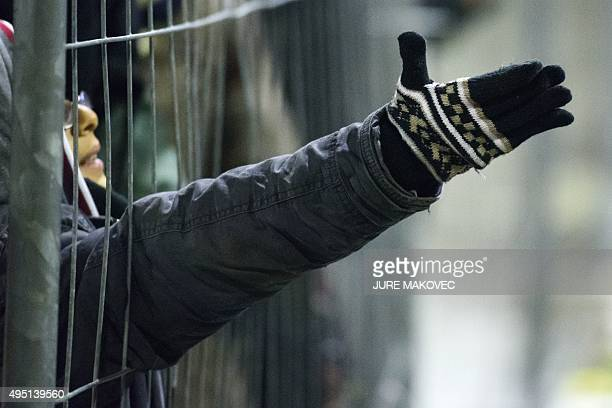 Migrants and refugees reach through a fence for food from volunteers as they wait to cross the SlovenianAustrian border in Sentilj on October 31 2015...