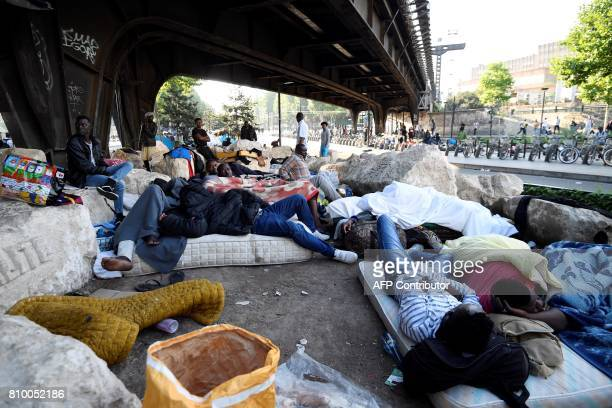 Migrants and refugees rest on the ground and on mattresses by a railway bridge during the evacuation of a makeshift camp at Porte de la Chapelle...