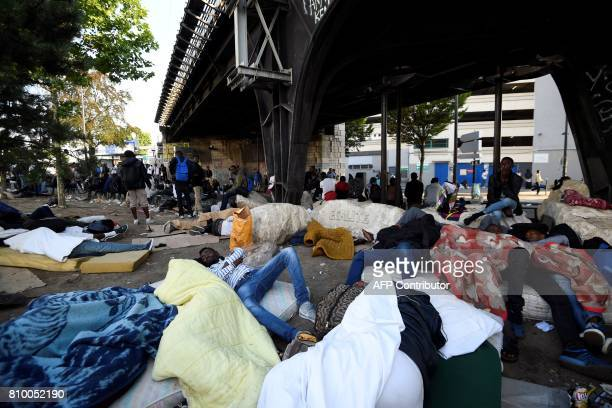 TOPSHOT Migrants and refugees rest on the ground and on mattresses by a railway bridge during the evacuation of a makeshift camp at Porte de la...