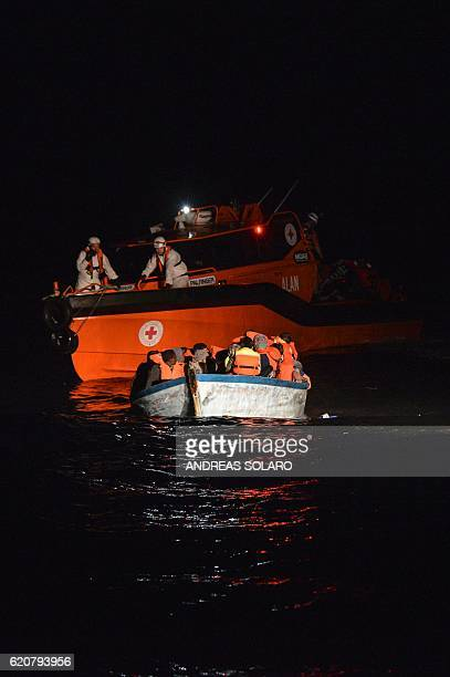 Migrants and refugees seated in a wooden boat wait to be rescued by Maltese NGO MOAS and the Italian Red Cross during an operation of rescue ship...