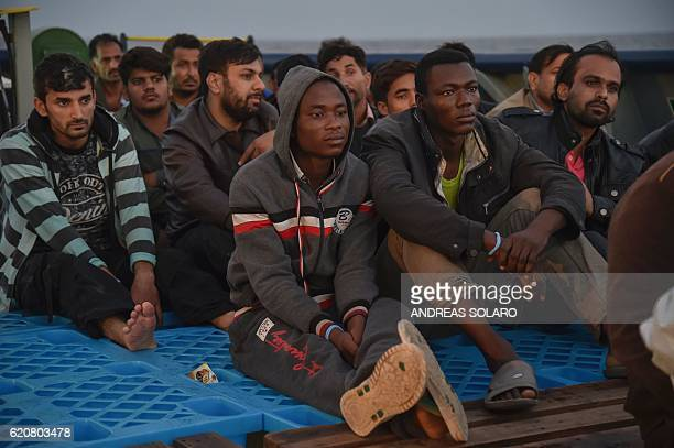 Migrants and refugees sit aboard the rescue ship Topaz Responder run by Maltese NGO Moas and Italian Red Cross during a rescue operation off the...
