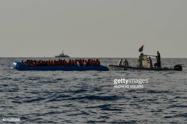 Migrants and refugees sit on a rubber boat as the Libyan coastguards patrol during a rescue operation of the Topaz Responder a rescue ship run by...