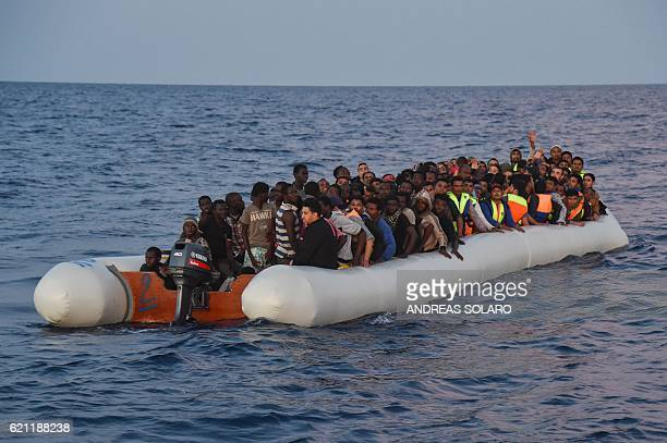 Migrants and refugees sit on a rubber boat before to be rescued by the ship Topaz Responder run by Maltese NGO Moas and Italian Red Cross off the...