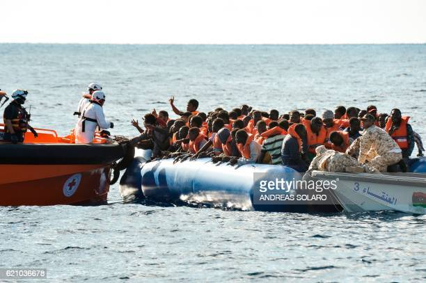 TOPSHOT Migrants and refugees sit on a rubber boat during a rescue operation of the Topaz Responder a rescue ship run by Maltese NGO Moas and the...