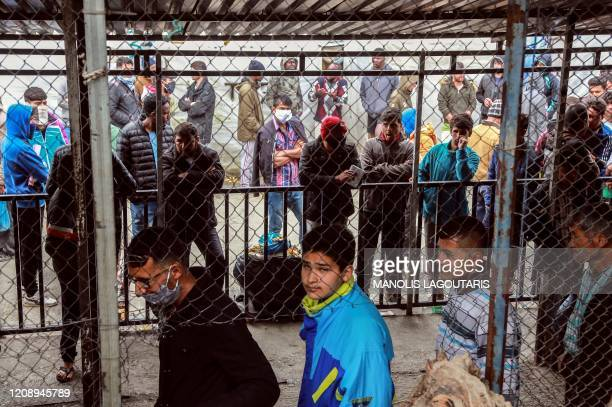 Migrants and refugees some wearing facemasks for protective measures queue in a makeshift camp next to the Moria camp on the Greek island of Lesbos...