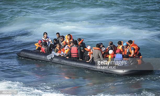 Migrants and refugees travel on a dinghy to the Greek island of Chios from Cesme in the Turkish province of Izmir on November 3 2015 Amnesty...