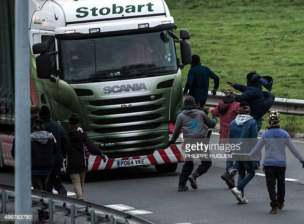 TOPSHOT Migrants and refugees try to block a truck on one of the access road for the Eurotunnel on December 3 2015 in Coquelles France's prisons...