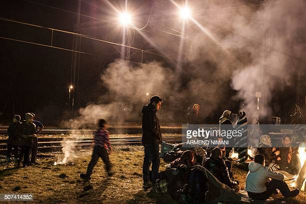 Migrants and refugees try to keep warm by a fire as they wait for a train after crossing the Macedonian border into Serbia near the town of Presevo...