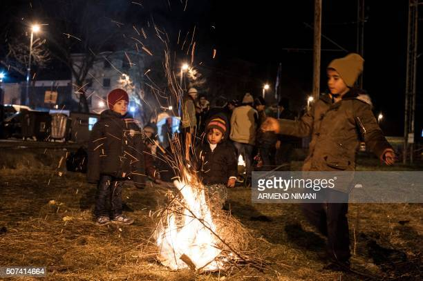 Migrants and refugees try to keep warm by a fire as they wait for a train after crossing the Macedonian border into Serbia, near the town of Presevo,...