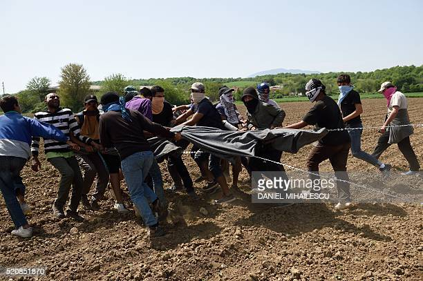 Migrants and refugees use blankets to pull razor wire from the border fence between Greece and Macedonia at the makeshift camp near the Greek village...