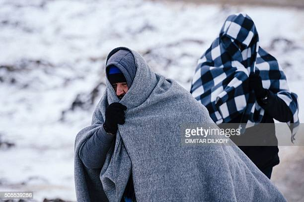 Migrants and refugees use their sleeping blankets to keep warm as they walk along snow covered tracks after crossing the Macedonian border into...