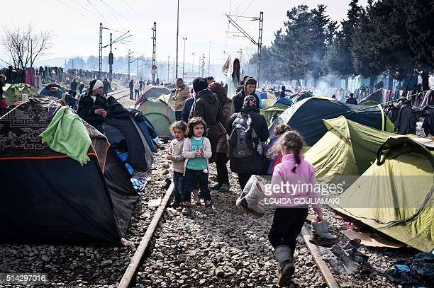 Migrants and refugees wait at the makeshift camp of the GreekMacedonian border near the village of Idomeni on March 8 where thousands of refugees and...