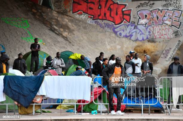 Migrants and refugees wait by their tents for the start of the evacuation of the Millenaire makeshift camp along the Canal de SaintDenis near Porte...