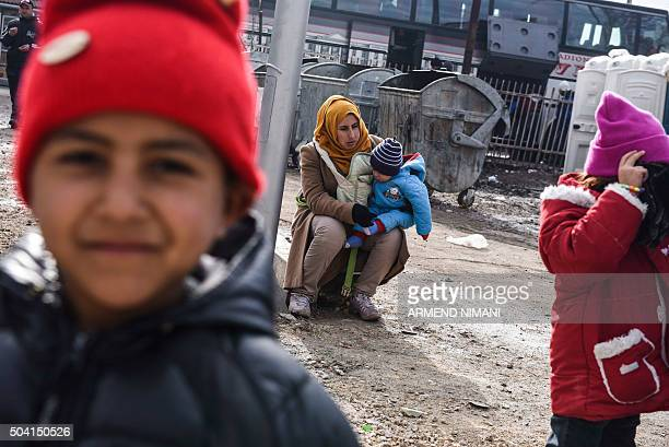 Migrants and refugees wait for a bus at a transit camp in southern Serbian town of Presevo on January 9, 2016. More than a million refugees and...