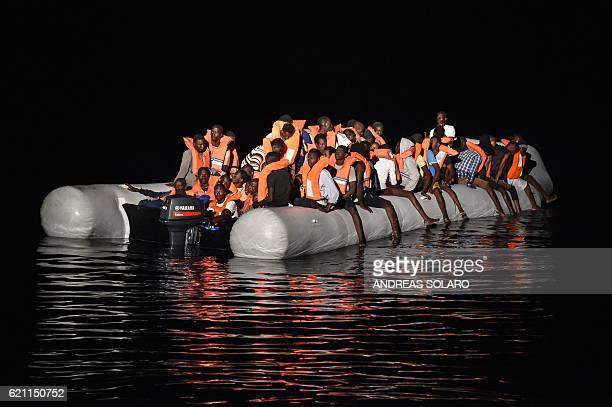 Migrants and refugees wait for further assistance during a rescue operation by the Topaz Responder ship run by the Maltese NGO Moas and the Italian...