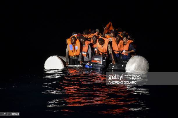 Migrants and refugees wait for further assistance during a rescue operation by the Topaz Responder ship, run by the Maltese NGO Moas and the Italian...
