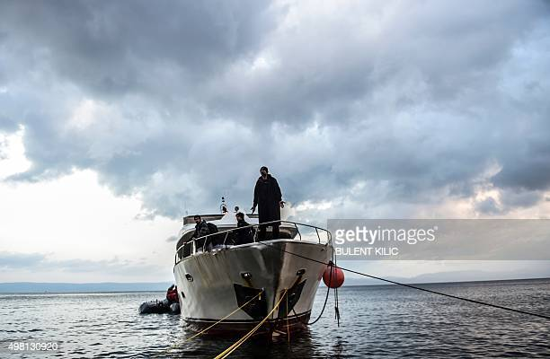 Migrants and refugees wait for help as they arrive on a boat on the Greek island of Lesbos after crossing the Aegean Sea from Turkey on November 21...