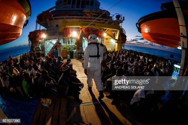 TOPSHOT Migrants and refugees wait to be trasferred from the Topaz Responder ship run by Maltese NGO Moas and the Italian Red Cross to the Vos Hestia...