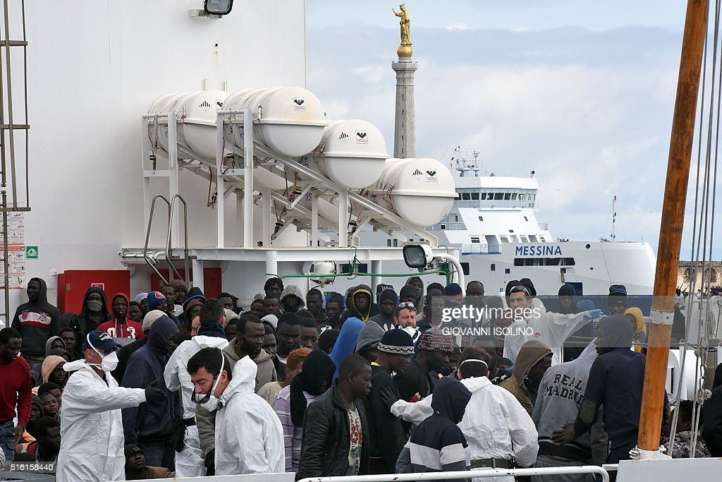 Migrants and refugees wait to disembark in the port of Messina