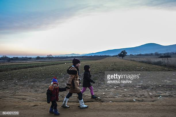 Migrants and refugees walk after crossing the Macedonian border into Serbia near the village of Miratovac on January 8 2016 More than a million...