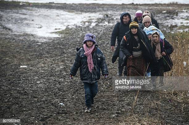 Migrants and refugees walk after crossing the Macedonian border into Serbia near the village of Miratovac on January 27 2016 More than one million...