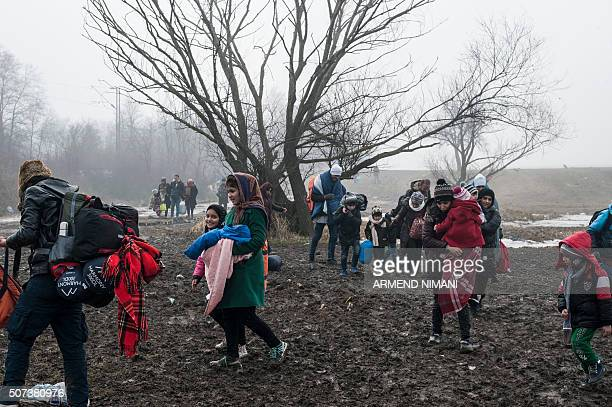 Migrants and refugees walk after crossing the Macedonian border into Serbia near the village of Miratovac on January 29 2016 More than one million...
