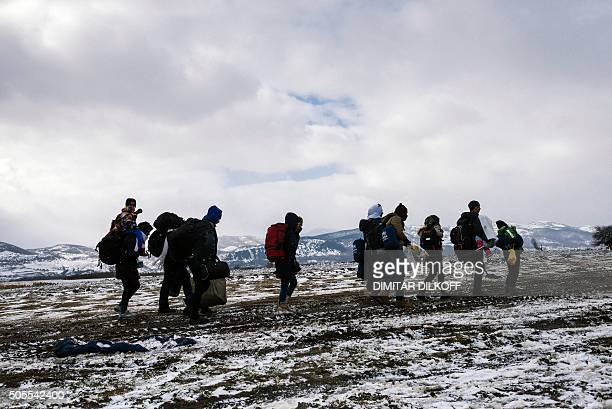 Migrants and refugees walk along snow covered tracks after crossing the Macedonian border into Serbia, near the village of Miratovac, on January 18,...