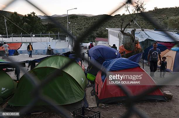 Migrants and refugees walk in the Moria camp on the island of Lesvos on September 20, 2016. AFP PHOTO /Louisa Gouliamaki Thousands of migrants were...