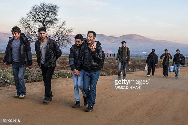 Migrants and refugees walk on a road after crossing the Macedonian border into Serbia near the village of Miratovac on January 8 2016 More than a...