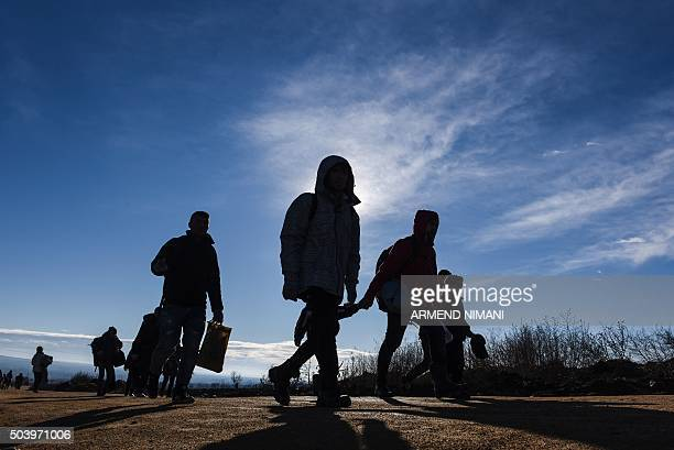 Migrants and refugees walk on January 8, 2016 after crossing the Macedonian border in the Serbian village of Miratovac. Migrants and refugees are...