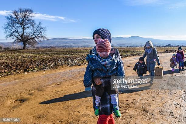 TOPSHOT Migrants and refugees walk on January 8 2016 after crossing the Macedonian border in the Serbian village of Miratovac Migrants and refugees...