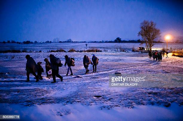 Migrants and refugees walk through a snow covered field after crossing the Macedonian border into Serbia near the village of Miratovac on January 17...