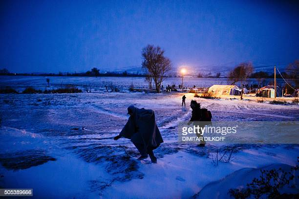 Migrants and refugees walk through a snowcovered field after crossing the MacedonianSerbian border near the village of Miratovac on January 17 2016...