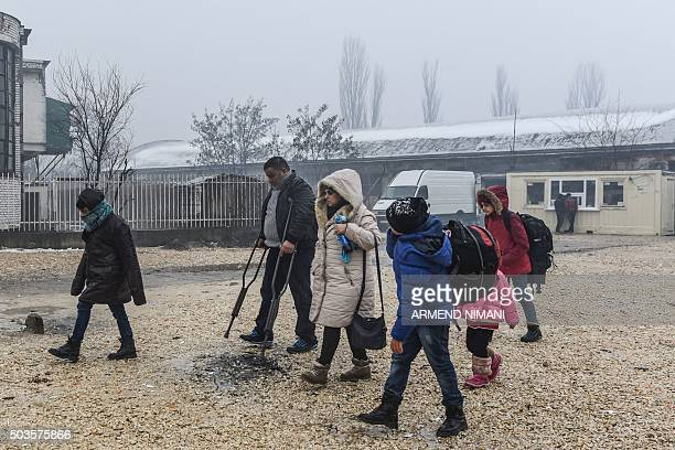 Migrants and refugees walk to board a bus heading to Croatia from the southern Serbian town of Presevo on January 6 2016 The International...