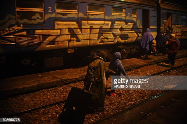 Migrants and refugees walk to board a train under heavy rain at a train station in the southern Serbian town of Presevo on January 6 2016 The...