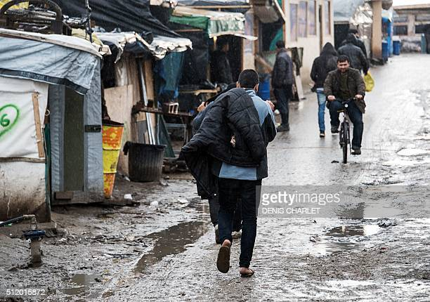 Migrants and refugees walk under the rain beside makeshift sheds in the socalled 'Jungle' refugee and migrant camp in Calais on February 24 2016 A...