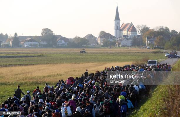 Migrants and refugees, who spent the night outdoors, are escorted by Slovenian soldiers and police officers as they walk towards a refugee camp after...