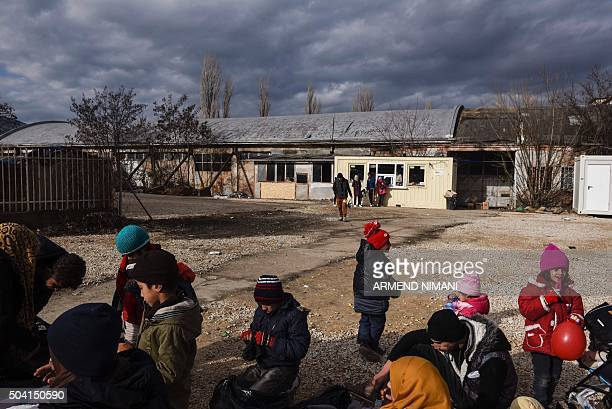 Migrants and refugees with their children wait for a bus at a transit camp in southern Serbian town of Presevo on January 9 2016 More than a million...