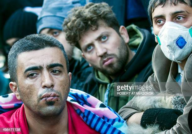 Migrants and refugees with their mouths sewn shut and claimed to be from Iran sit on railway tracks as they wait to cross the GreekMacedonian border...