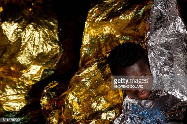 """Migrants and refugees wrapped in survival blankets wait to be transferred from the Topaz Responder ship run by Maltese NGO """"Moas"""" and the Italian Red..."""