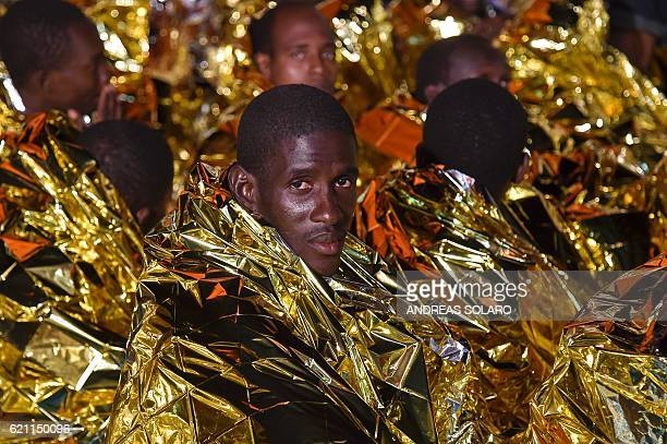 Migrants and refugees wrapped in survival foil blankets look on during a rescue operation by the Topaz Responder ship run by Maltese NGO Moas and the...