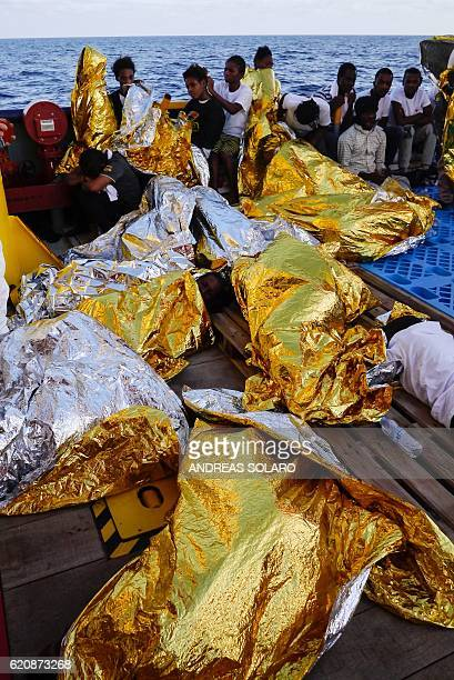 Migrants and refugees wrapped in survival foil blankets rest aboard the Topaz Responder ship run by Maltese NGO Moas and the Italian Red Cross after...