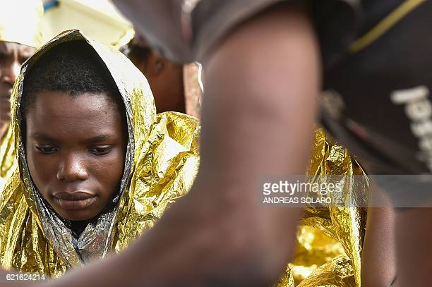 Migrants and refugees wrapped in survival foil blankets rest aboard the Topaz Responder ship run by Maltese NGO Moas and the Red Cross before to...